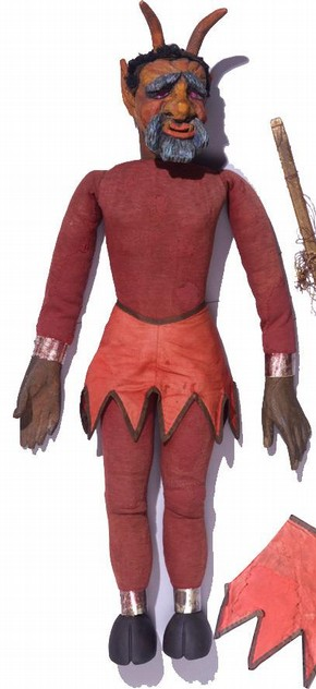 A 19th century marionette of the devil, Theatre Museum. The skirt is a satin weave cotton, which has been repaired using a neutral coloured fabric and couch stitching. Museum no. S.305-1999