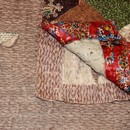 Figure 12 - Patchwork and quilted bedcover, 1810-45, England. Museum no. T.17-1924. Detail of wool flannel and woollen blanket seen through a hole in the lining and where the lining was loose at one corner.