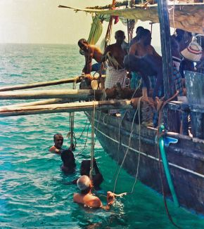 Pearl divers holding onto the rope attached to the collecting baskets, reproduction of original photograph. © Qatar News Agency Archives