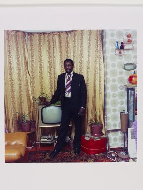 Neil Kenlock, 'Untitled [A well fully clad man photographed standing by his television in Stockwell, South London]', 1923. Museum no. E.215-2012. © Neil Kenlock/ Victoria and Albert Museum, London. Supported by the National Lottery through the Heritage Lottery Fund.
