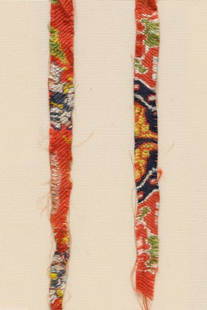 Two fragments of red patterned silk, 700–900. Museum no. LOAN:STEIN.301:1, 2