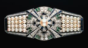 Sash clip 'Yaguruma' (Wheels of Arrows) and box, Mikimoto, Japan, 1937, platinum, 18 carat white gold, cultured Akoya pearls, diamonds, sapphires and emeralds. © Mikimoto Pearl Island, Japan