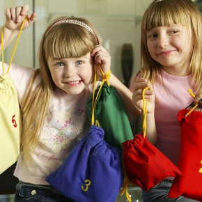 Children holding up the contents of a V&A activity backpack.