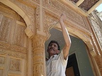 Photograph of a trained craftsman at work restoring a traditional courtyard house.  Shahed Saleem 