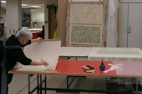 Figure 2 - Lining and drying William Morris wallpaper samples on karibari board. Photograph by Sophie Connor, November 2010