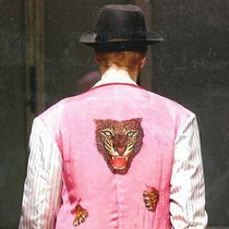 Yuzen dyed emblem of a tiger's head and paws on inside-out pink silk coat and grey wool trousers, Yohji Yamamoto, Autumn/Winter 2009-10. © Courtesy of Monica Feudi