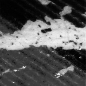 Figure 1. This crack in the image layer of a colour photocopy occurred after folding the paper just twice. Note the splintering of the brittle toner. (magnification x60 approx.)