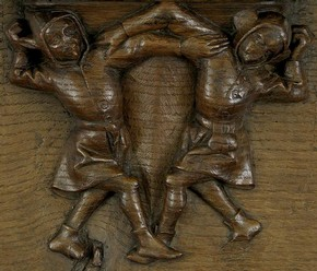 Two jesters dancing, carved aok misericord, Belgium, 1438-50. Museum no. W.29-1910