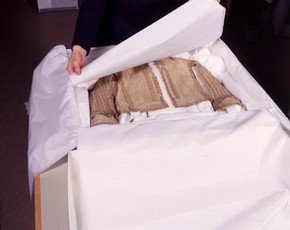 A historic costume stored in an box, with acid-free tissue.
