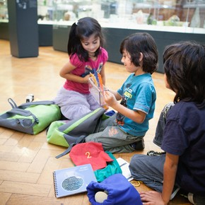 Family working with the V&A activity backpack in the glass gallery.