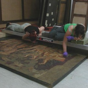 Figure 1. Students using a bridge to clean one of the larger paintings. Photography by Nicola Costaras.