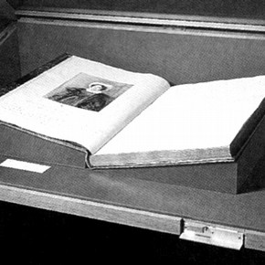 Figure 1. Book support made of museum board covered in the same cloth as the case lining, during installation. Photography by V