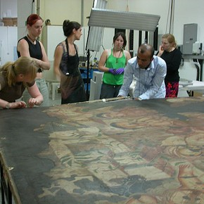 Figure 2. Students strip lining one of the paintings. Photograph by Nicola Costaras.