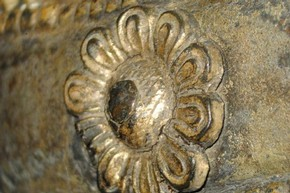 Figure 4 - Detail of a repousséd copper flower attached to the front of the gilded brass belt. Photography by Diana Heath