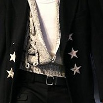 Dark navy blue and black coat with embroidered stars, white sleeveless top, beige cardigan and black trousers, Yohji Yamamoto, Autumn/Winter 2006-7.  Courtesy of Monica Feudi / Feudi e Guaineri