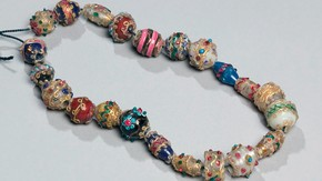 Necklace, Africa, before 1874, vVariegated glass beads and metal pendant. Museum no. 3-1875