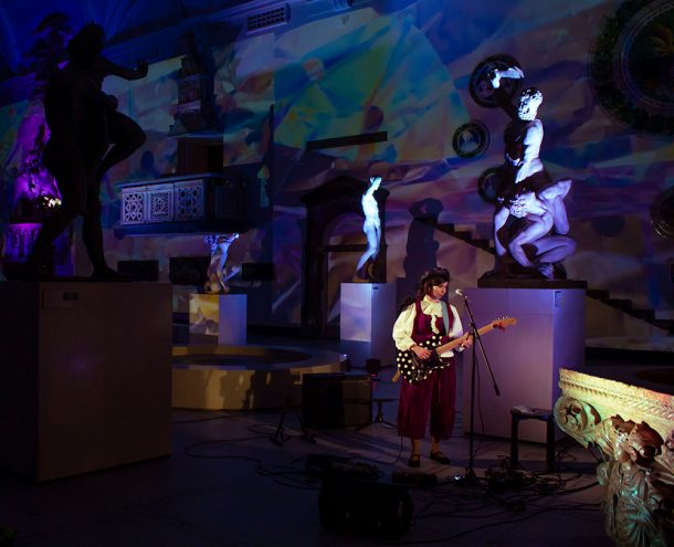 Nabihah Iqbal performing on her electric guitar, surrounded by sculptures in the Medieval and Renaissance gallery