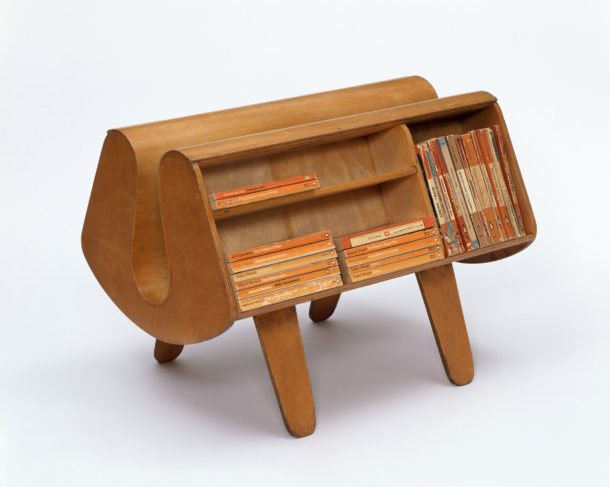 Small freestanding bookcase made of plywood designed to hold Penguin paperbacks. The bookcase resembles a pair of pannier set on four legs - this is why it was named the 'Donkey'.