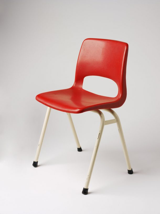 Red plastic school chair, with white metal legs