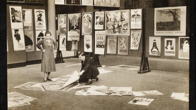 A woman and a man installing a poster exhibition at the V&A, Emil Otto Hoppé, 1931. E.655-1996