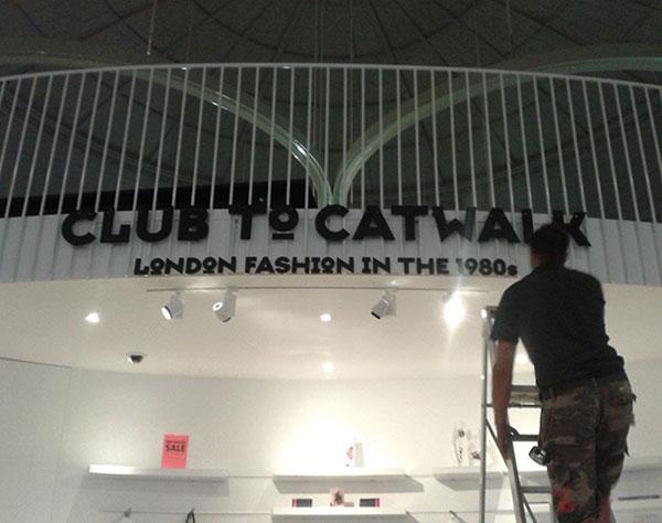 Workman installing Club to Catwalk sign