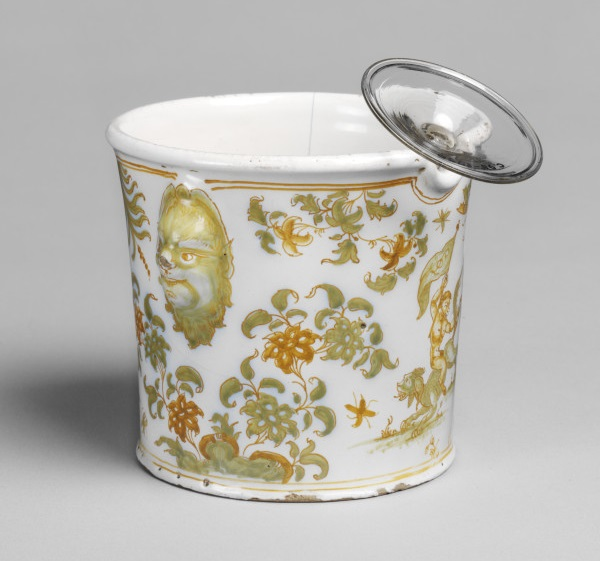 Tin-glazed earthenware wine glass cooler, cylindrical with two grotesque mask handles, Olérys and Laugier's pottery factory, Moustiers-Sainte-Marie, about 1739-1749 (V&A C.127-1930) © Victoria and Albert Museum, London