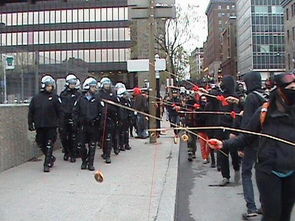 Montreal's student demonstrators wave donuts to distract riot police in 2012.  Many of their homemade fishing lines are decorated with red fabric, emblems of their struggle against tuition hikes.