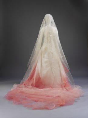 The dress train and veil fall in a romantic tangle behind