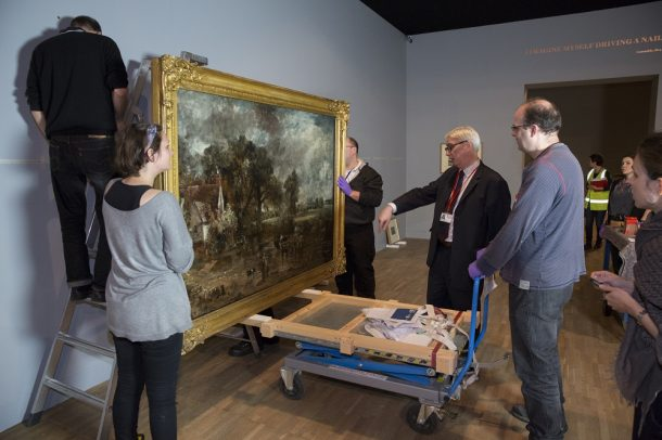 Curator Mark Evans works with technicians to install 'The Hay Wain' (full-size sketch).