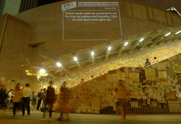 """One side of the protest site outside Hong Kong's Central Government Offices at Admiralty. From top to bottom: wall projection from """"Add Oil Machine for HK Occupiers"""", """"Lennon Wall"""", and numerous sketches and posters. © Becky Sun"""