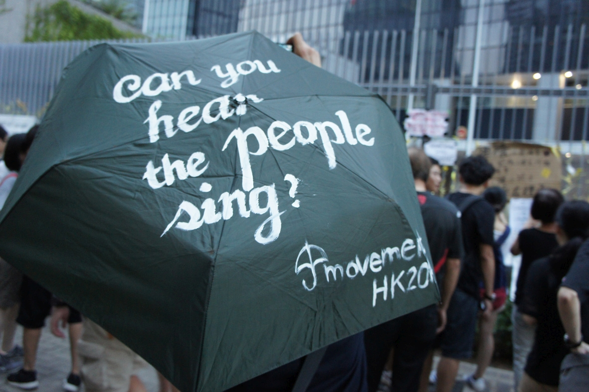 """One of the umbrellas with calligraphy by Savona Ling, outside the first """"Democracy Wall"""" on the tall fences encircling the Civic Square in the background. Civic Square, whose name was so given in a student movement against nationalist education in 2012, was fenced off in recent months for added security to the Central Government Offices."""