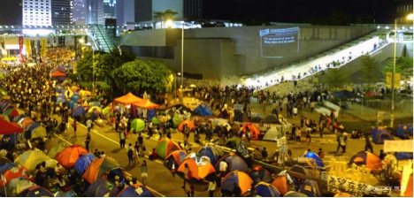 "Around 2,300 tents have been propped up around the Central Government Offices in Admiralty, Hong Kong. The wall projection is ""Add Oil Machine for HK Occupiers"" by artists including Sampson Wong Yu-hin and Jason Lam, which displays support messages collected via a website they custom built. Photograph by Becky Sun. © Becky Sun"