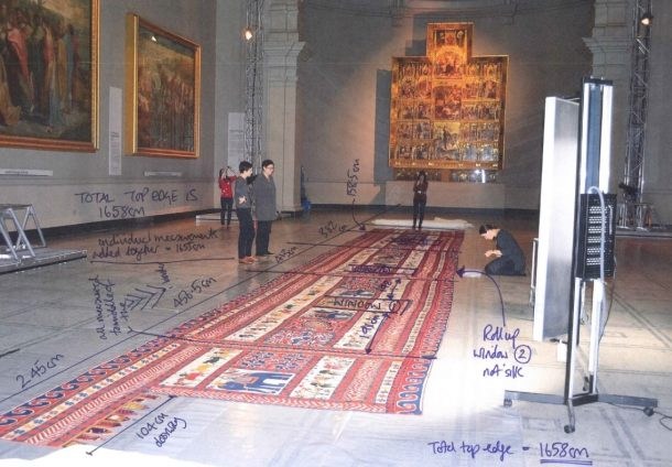 V&A Textile Conservator, Elizabeth-Anne Haldane writes her measurements directly onto a photo taken in the Raphael courts of the Wall hanging (bhitiya) made Saurashtra, India ca.20th century.
