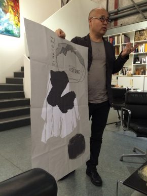 Bi Xuefeng showing one of his latest posters