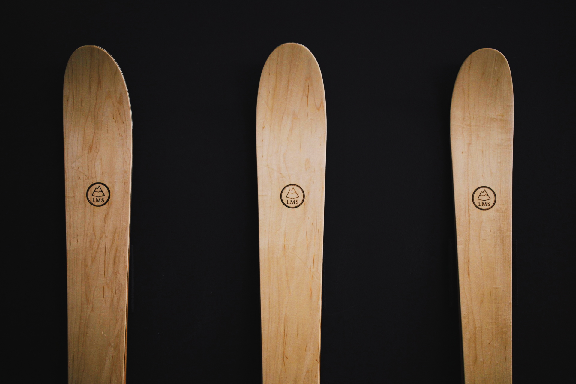 three beautiful wooden skis in a line against a black background