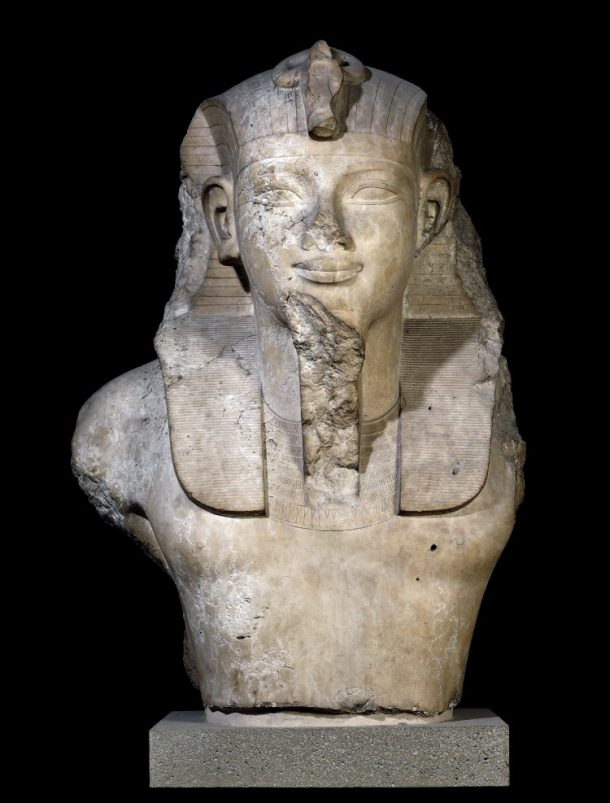 Head and upper torso of monumental limestone statue wearing nemes, probably Amenhotep III. Excavated at the temple of Amenhotep III © The Trustees of the British Museum
