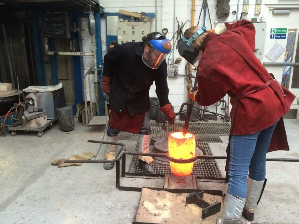 The crucible has been lifted out of the furnace and placed in an iron support.  Becky removes the slag (waste) from the motlen bronze in the crucible.