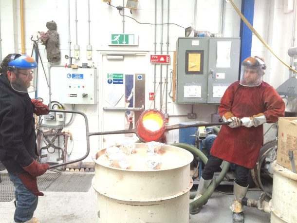 Drew and colleague raise the crucible and fill the moulds with bronze.