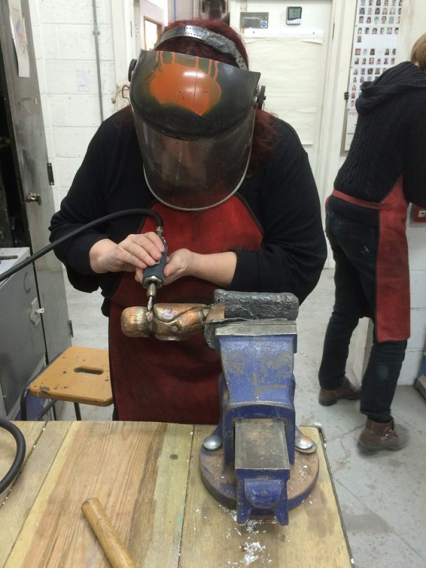 The head and body of the owl were cast separately and welded together by Drew.  Felicity is completing the process by which the two pieces were joined using an electric chisel.