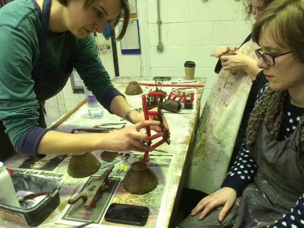 Sculptor and course leader Becky Whitmore assisting with the tricky business of attaching a system of wax runners and risers and a cup to the model.  These will eventually allow the bronze to be channelled down into the mould.
