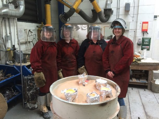The team in full protective gear in the foundry.  Our moulds, covered with an outer protective covering of foil, have just been filled with molten bronze.