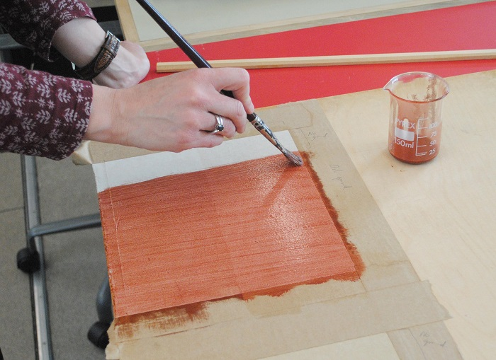 Applying the red-brown oil ground. You can already see how the paper is absorbing the oil where there is no sizing.