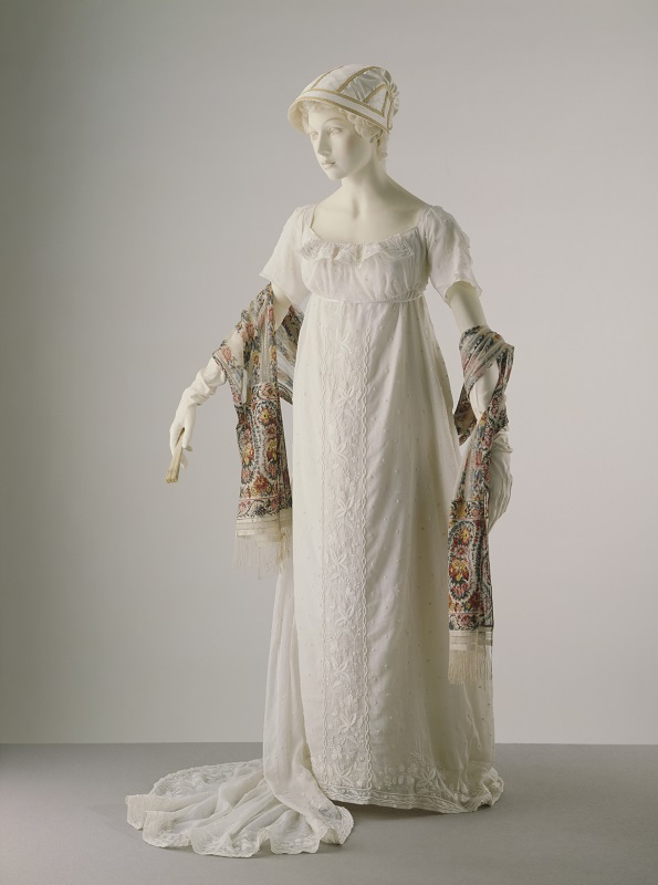 T.124-1913; 678-1893; T.246-1967 Evening dress; white muslin, embroidered all over in white cotton, French, c.1806; Scarf; printed knitted silk; English; c.1810. Fan; carved & pierced ivory; English; Early 19th century.