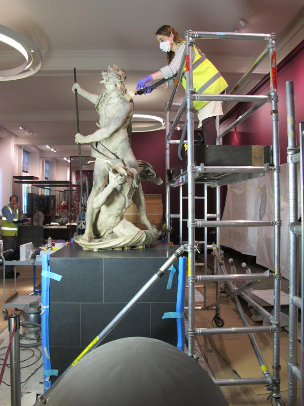 UCL student Vanessa Applebaum dusting the top part of the figure group © Johanna Puisto, Victoria and Albert Museum, London
