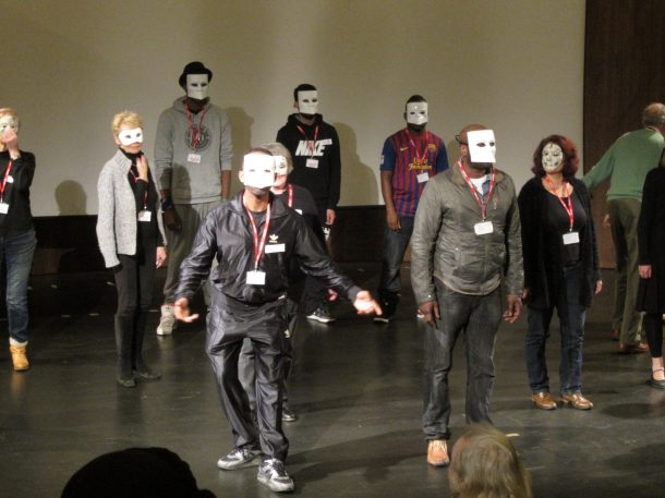 A workshop of people learning movement and mask-wearing
