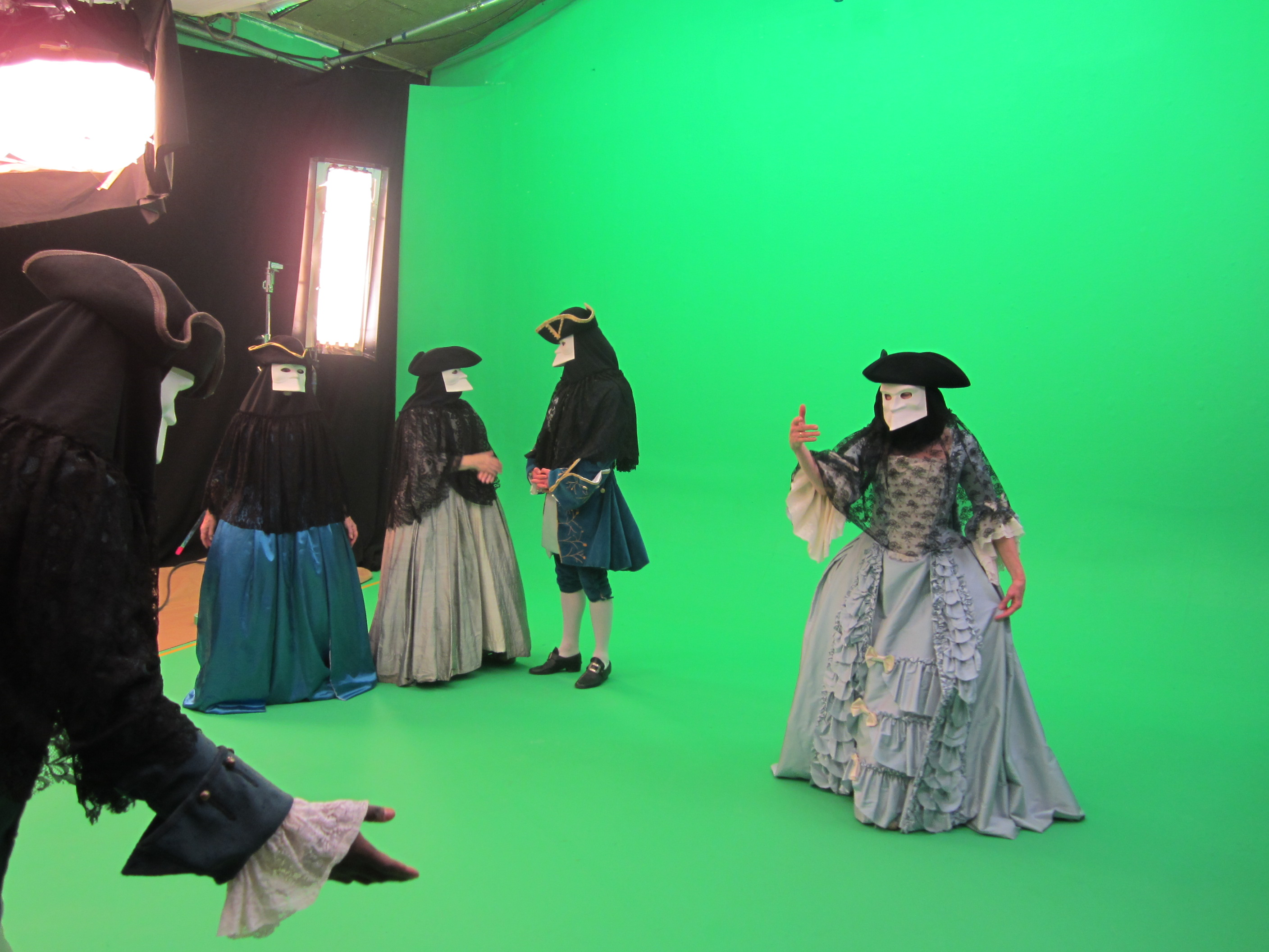 A cast in costume filming in front of a green screen