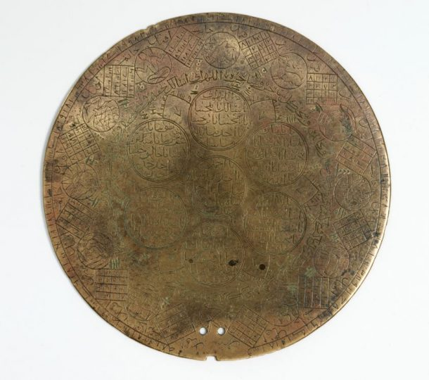 A close up of the engraved astrological disk which depicts the twelve zodiac signs, magic squares, a section of Al-Asma' al-Husna (Beautiful names of Allah), and the dot and lined figures created using the ilm al raml technique as seen in the first image. The two small holes at the bottom indicate the possibility of a handle attached to this object at some point in the past. © Victoria and Albert Museum