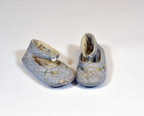 """MISC.605:1-1984; MISC.605:2-1984 Pair of baby slippers Paid of pale blue quilted slippers. Inserted card in one slipper inscribed """"Greetings to Mummy (to be) from Daddy (to be)"""". British 1938 Chilprufe Ltd. British 1938 Rayon, cotton, silk, Pair of baby slippers Paid of pale blue quilted slippers. Inserted card in one slipper inscribed """"Greetings to Mummy (to be) from Daddy (to be)"""". British 1938 Chilprufe Ltd. British 1938 Rayon, cotton, silk,"""