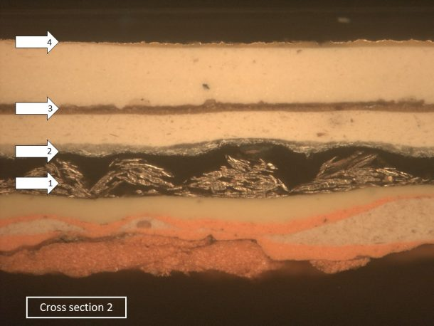 Figure 2: One of the cross sections from the Angel, viewed under the microscope, showing the layers of paint and metal. The arrows indicate the metallic finishes.