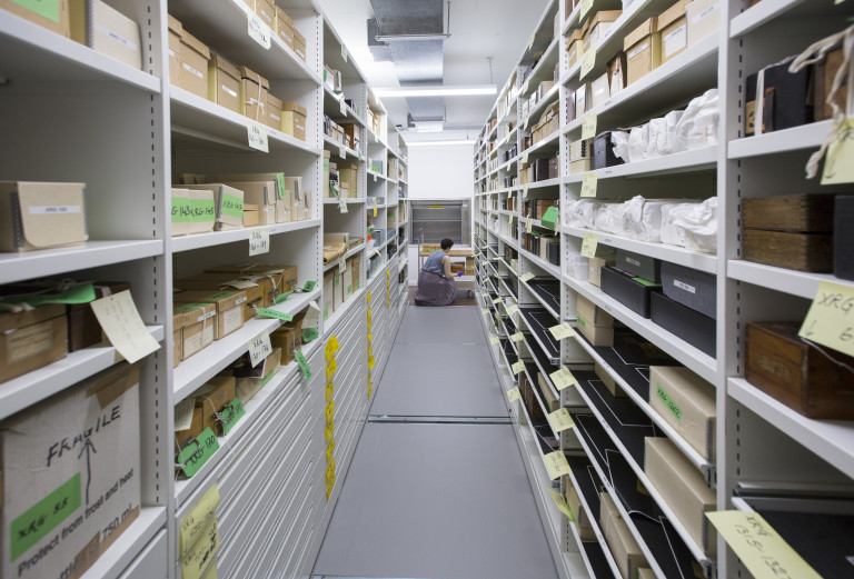 Image of a woman kneeling by a trolley in an aisle of museum storage